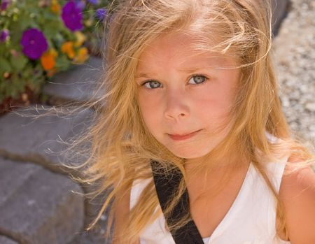 bi racial: This cute 4 year old bi-racial girl is outdoors with her blond hair wisping around her cute face.