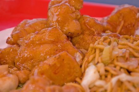 This dish is the Chinese food sweet and sour deep fried chicken with some chow mein to the side.