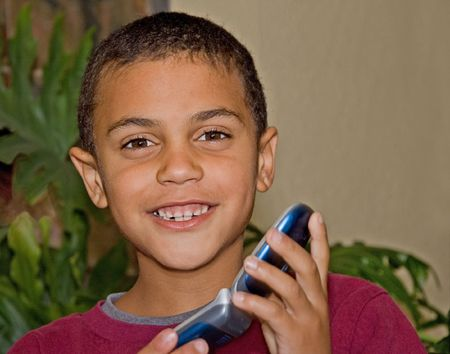 bi racial: This cute 9 year old bi-racial boy is smiling and happy with a cell phone.