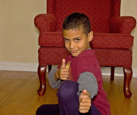 next year: This handsome 9 year old bi racial boy is next to a chair smiling with a thumbs up pose. Stock Photo