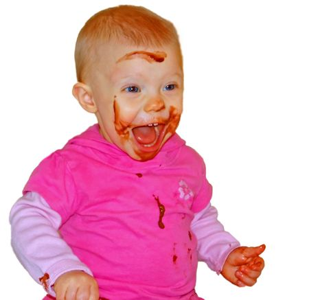 This cute Caucasian baby is having a great time while playing in chocolate pudding and making a huge mess isolated on a white background. photo