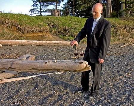 This young groom is pouring red wine into two glasses on a log on a beach, waiting for his bride. Stock Photo - 5593445