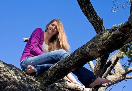 over the shoulders: This pretty teen girl with long hair is sitting barefoot in a tree against bright blue sky.