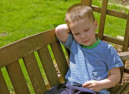 This 4 year old little boy is sitting relaxing on a wooden garden swing.  He is very quiet and still in this photo. photo