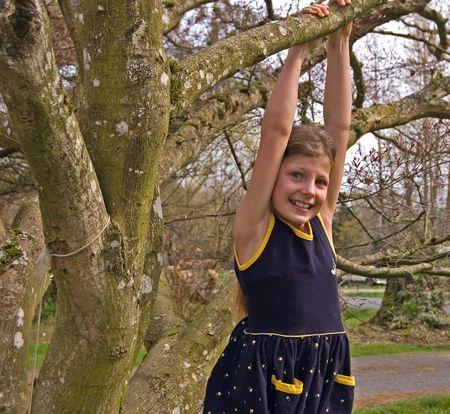 꽤 8 살짜리 소녀는 해군 파란색 드레스에 나무에서 매달려있다. 그녀는 걱정되는 얼굴 표정을 가지고 있습니다.