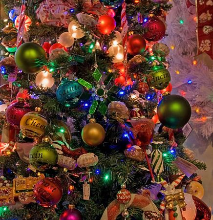 This Christmas tree is decorated heavily with many different colored ornament balls and lights. photo