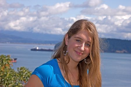 This pretty teen with blue eyes wearing a blue shirt has an ocean with a barge ship in the background. photo