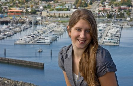 This pretty teen is smiling and happy with a beautiful marina in the distance. photo