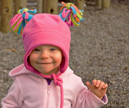 pink hat: Beautiful toddler girl wearing a hot pink hat with multi colored tassels is biting her lip in an apprehensive expression.
