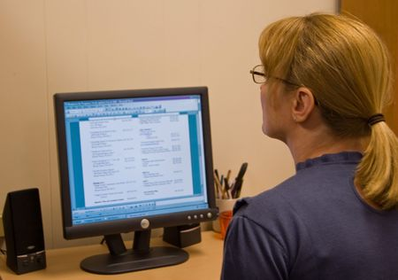 work station: A middle aged woman is at her computer work station working in a clerical positioned job. Stock Photo
