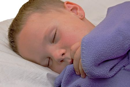 This cute 5 year old Caucasian boy with freckles and an earring is sleeping on his bed with pillow and purple blanket.