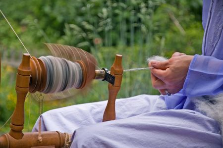 This is a closeup of a spinning wheel in motion of hand spun yarn made from alpaca wool.