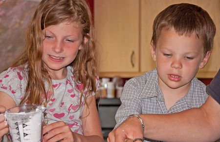 This brother and sister are cooking in the kitchen and enjoying measuring ingredients. photo