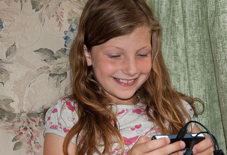 This young girl is happy and smiling while playing a video game. photo
