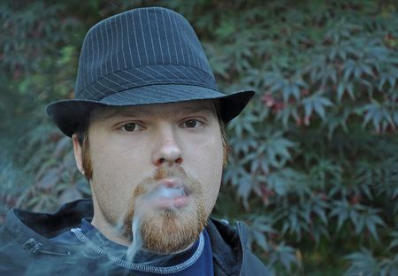 This young Caucasian man with goatee and wearing a black pin striped hat is blowing smoke. photo