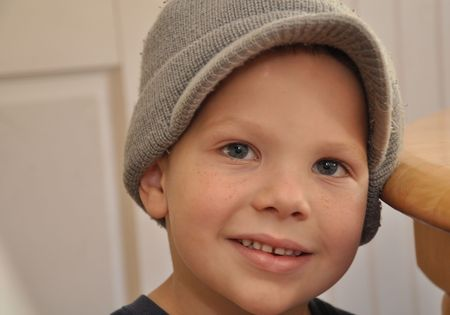 cute 5 year old Caucasian boy with freckles wearing a gray hat. photo