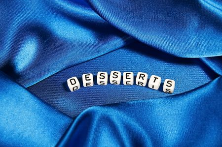 This series has a royal blue shiny background with the word desserts in black and white cube lettering. photo