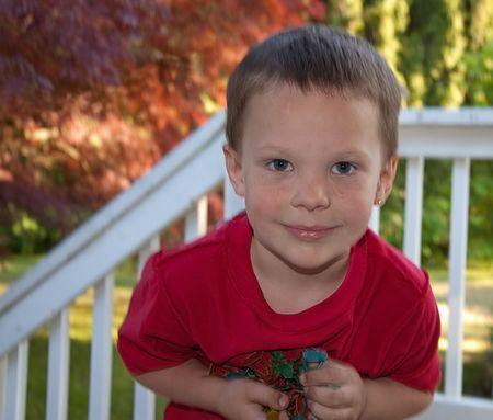 Este lindo azul ojos 5 a�o de edad del C�ucaso ni�o est� jugando y celebraci�n de pl�stico juguetes outdooors. Foto de archivo