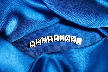 Royal blue satin background with rich folds and wrinkles for texture is the word Breakfast in black and white cube lettering in this cookies series. photo