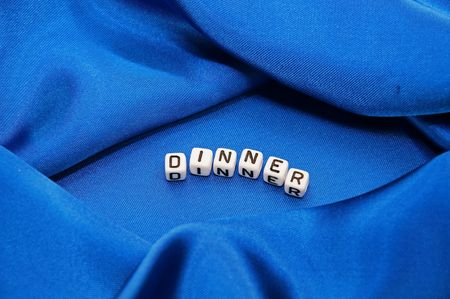 Royal blue satin background with rich folds and wrinkles for texture is the word dinner in black and white cube lettering in this cooking series. Banco de Imagens