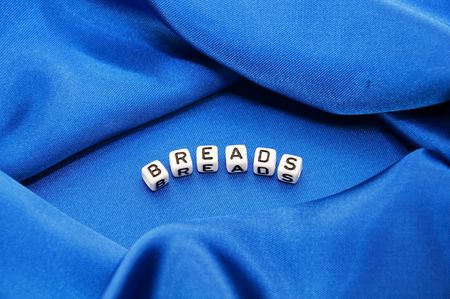 Royal blue satin background with rich folds and wrinkles for texture is the word breads in black and white cube lettering in this cooking series. Stock Photo - 5767949