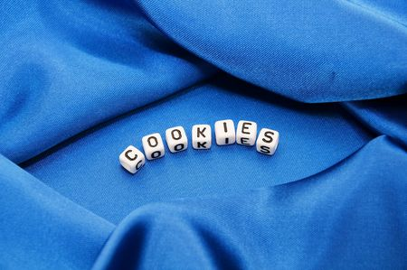 Royal blue satin background with rich folds and wrinkles for texture is the word cookies in black and white cube lettering in this cooking series. photo