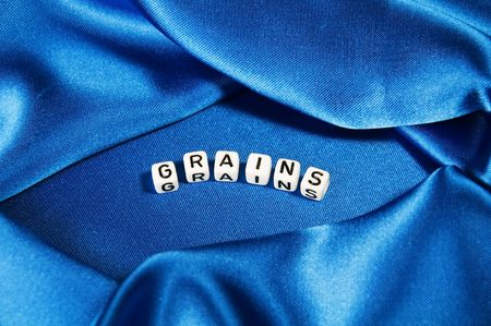 Royal blue satin background with rich folds and wrinkles for texture is the word grains in black and white cube lettering in this cooking series. photo