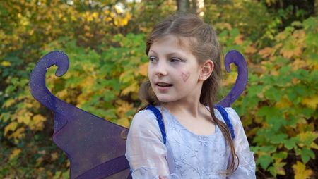 This cute 9 year old girl is wearing a ferry princess costume outdoors against fall leaves in a Halloween outfit. photo