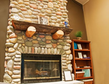 This beautiful tall stone fireplace is featured in a corner of an interior room for a cozy warm feeling. Stock Photo - 5810163