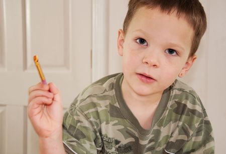 5 year old: This little boy is holding a paint brush loaded with paint as hes enjoying his hobby.