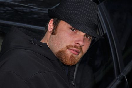 This young Caucasian man has a red goatee and wearing a black pin striped hat while leaning against a black car with a mysterious type facial expression. photo