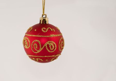 This photo has one red Christmas ball ornament hanging from a gold thread isolated on a white background. Stock Photo - 5904831