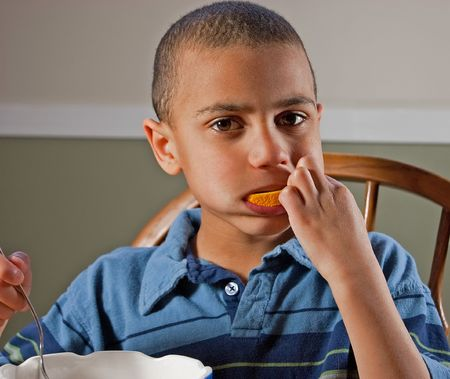 bi racial: This cute 9 year old bi-racial boy is sitting at a table and eating an orange for a healthy snack.