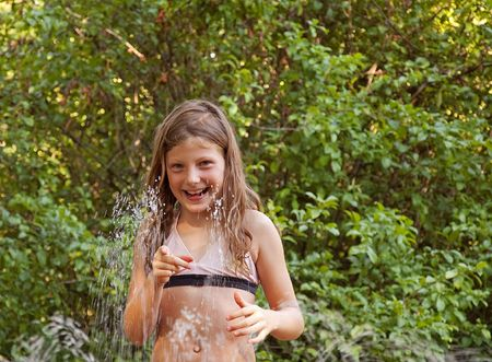 This cute girl is playing in the sprinkler in summer to cool off with lots of green leaves in the background.  Fun childhood summer moments. photo