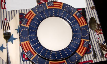 This photo shows an old American style place setting with fork, knife, spoon, plates, napkins and placemat in red white and blue theme. photo