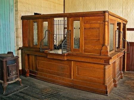 replication: This antique bank teller station is an authentic replication with old wooden floors and wood stove to the old black typewriter in the background.