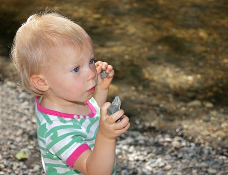 This cute little toddler has her hands full of rocks at the beach. photo