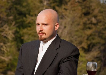 This groom is outdoors with a glass of red wine nearby with an anxious facial expression and emotion. photo