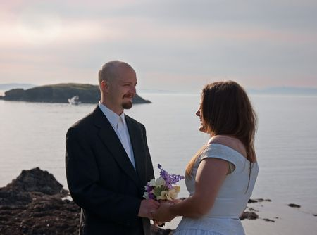 This happy groom with his bride are at the beach at sunset for a very romantic photo. photo