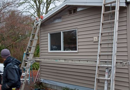 house siding: This exterior home renovation project has ladders and scaffolding in the midst of this project.  Construction worker is off to the side of this photo. Stock Photo