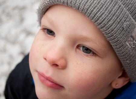 Dieses Foto ist eine Großaufnahme des ein hübsch kleiner junge Gesicht im Winter mit einer Kappe Strumpf auf und rosigen Wangen mit seiner Sommersprossen. Standard-Bild - 6100858