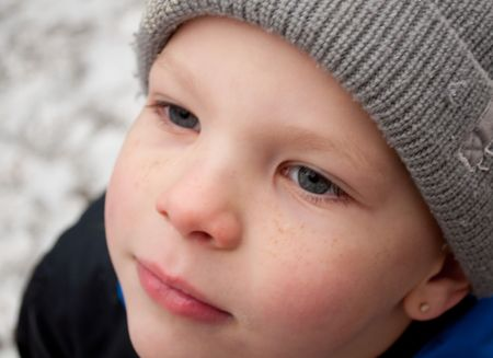 This photo is a closeup of a cute little boys face in winter with a stocking cap on and rosy cheeks with his freckles. photo