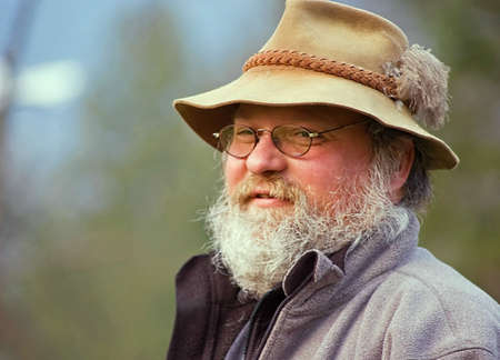 graying: This photo is a Caucasian middle aged hillbilly rugged mountain man type person.  Raggy gray beard and rustic hat top the look.