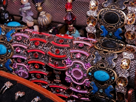 A display with rows of costume jewelry in reds, purples, blues in bracelets and rings. Stock Photo