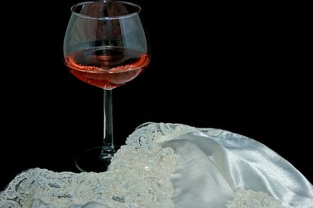 silky lingerie: This still life is an ultimate romantic scene with a glass of blush or pink wine with a beautiful white lingerie against a black background.