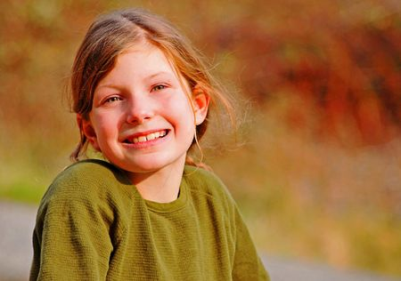 Young Caucasian girl smiling, long brown hair, green eyes and wearing a green shirt. photo
