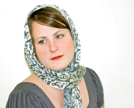 This attractive young Caucasian woman is wearing a gray patterned scarf against a light background. photo