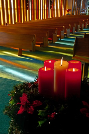 This vertical stock image is lit red and white Christmas candles in an evergreen wreath with holly and Poinsettias with an empty church with rows of wooden pews softly in the background.  Sunlight is shining through stained glass windows.  Beautiful, peac