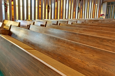 This stock image has rows of empty wooden church pews with sunlight filtering through the vertical stained glass windows. Editorial