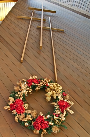 This stock image has three crosses with a view of looking up at the crosses from the foot of the cross inside a portion of a church.  There is a gold and red Christmas wreath hanging beneath the crosses.